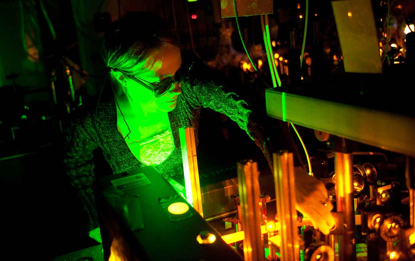 woman working in green glow of optical equipment
