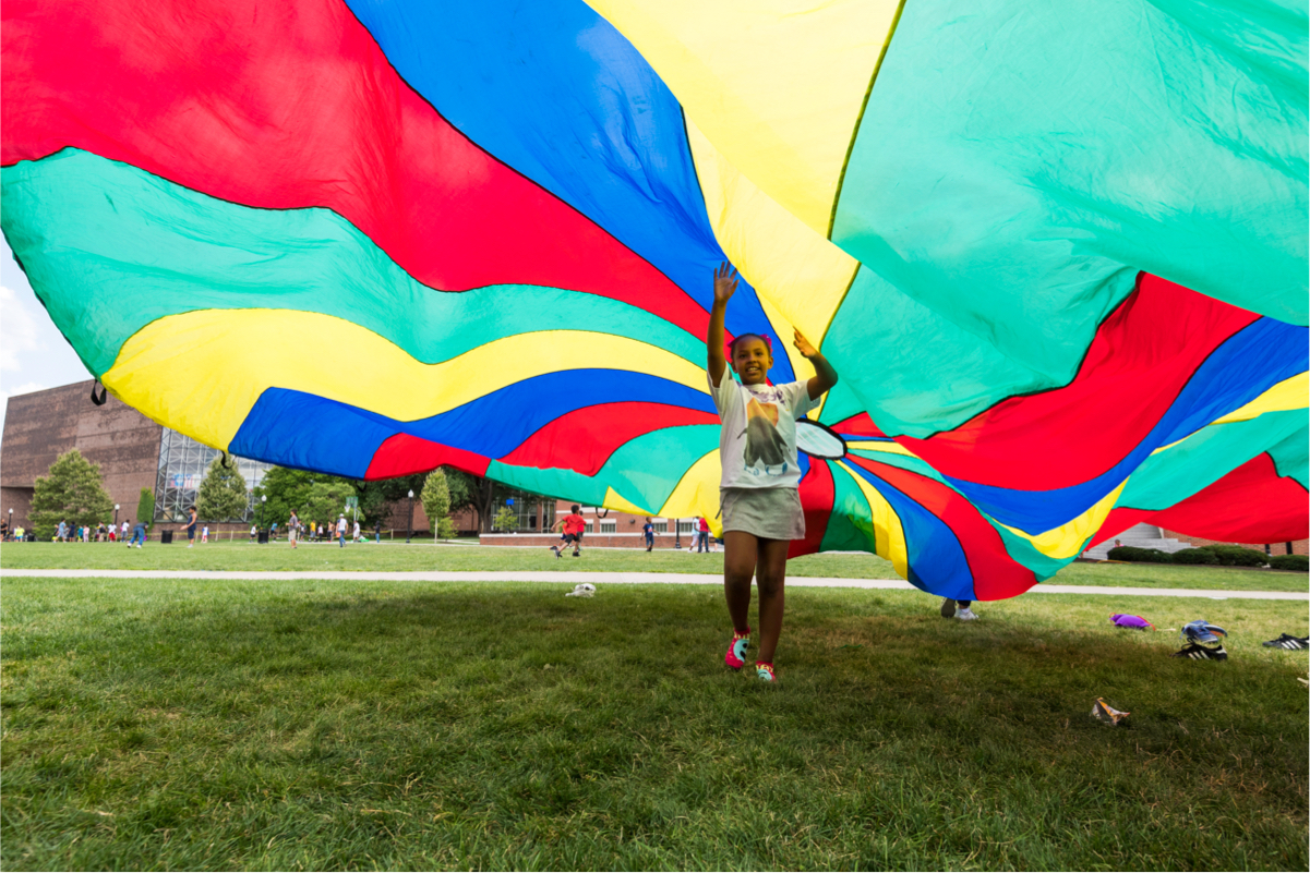 Young child runs under parachute at University of Rochester