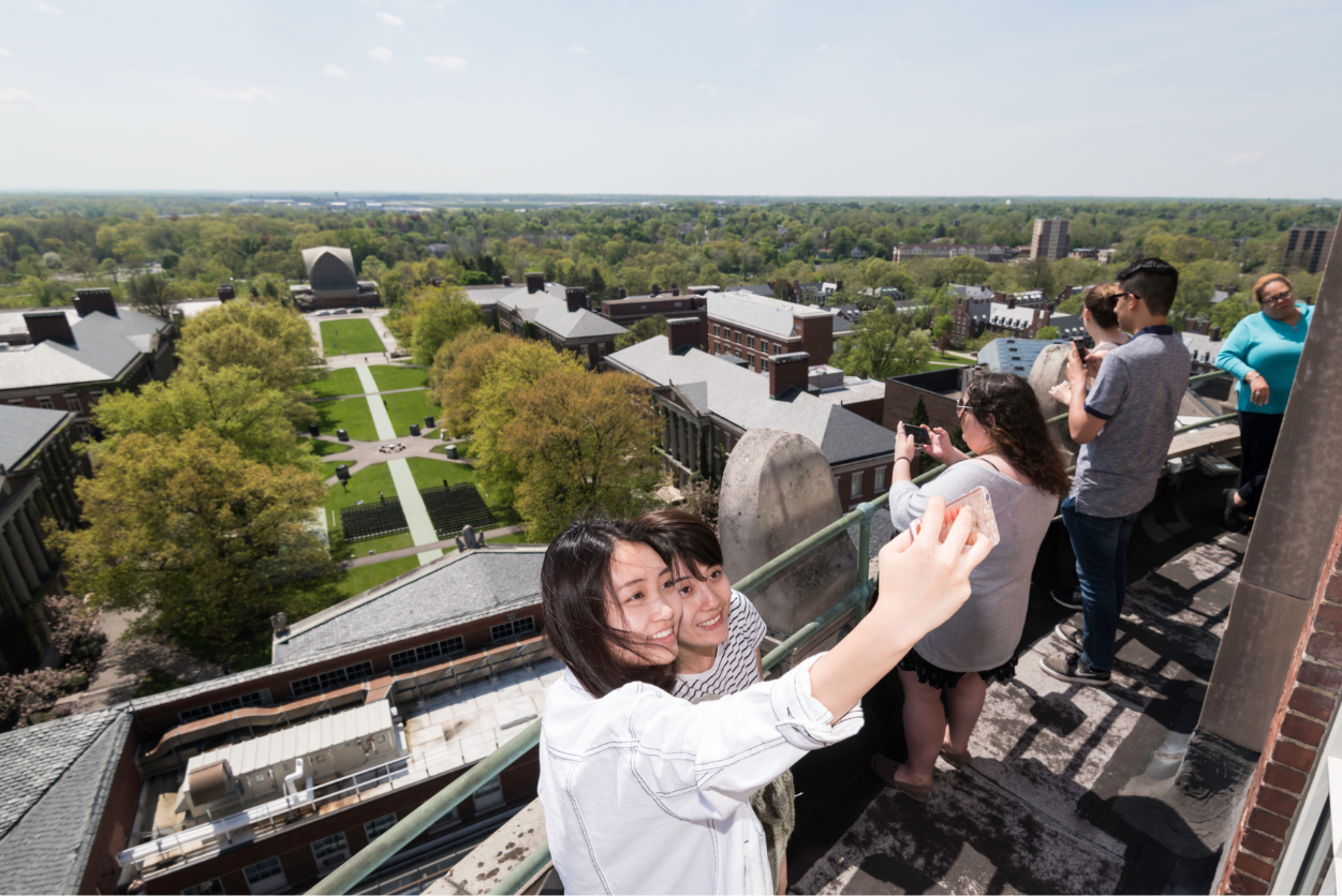 Students taking selfie overlooking University of Rochester from the top of Rush Rhees Library
