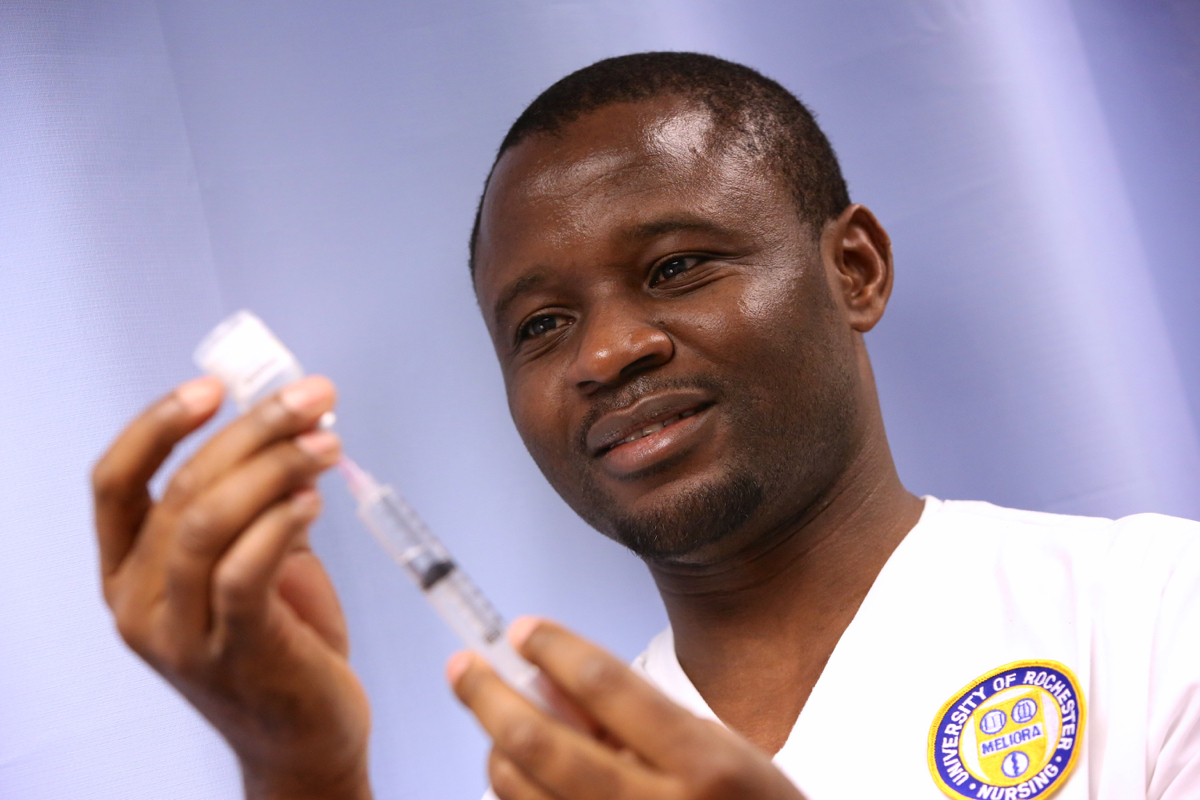 University of Rochester employee uses a syringe