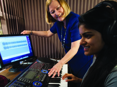 Elizabeth West Marvin, Eastman School of Music professor of music theory and brain and cognitive sciences, with Vasha Nair '14E in a soundproof booth