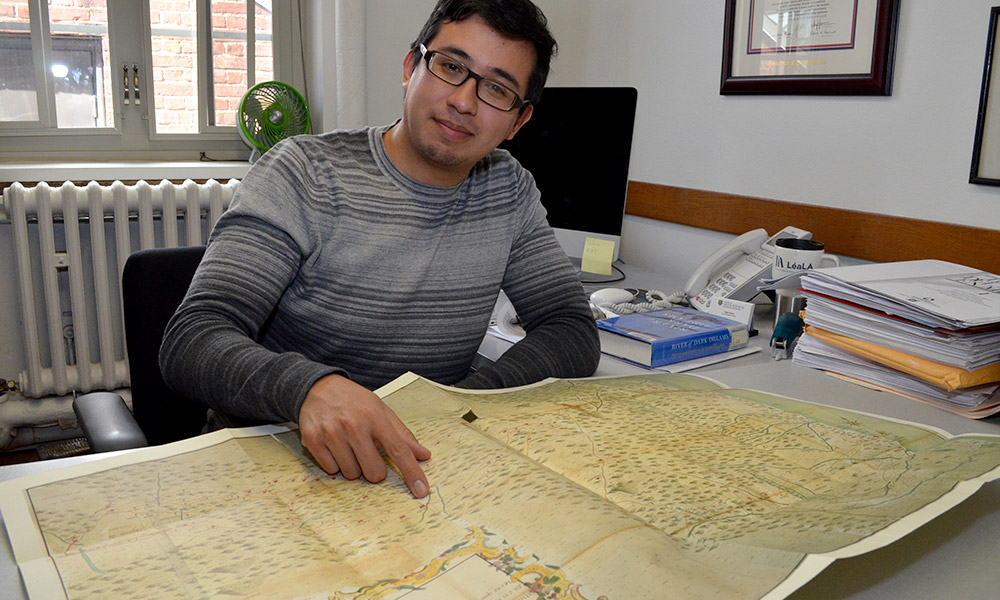 Pablo Sierra in his office, points to map