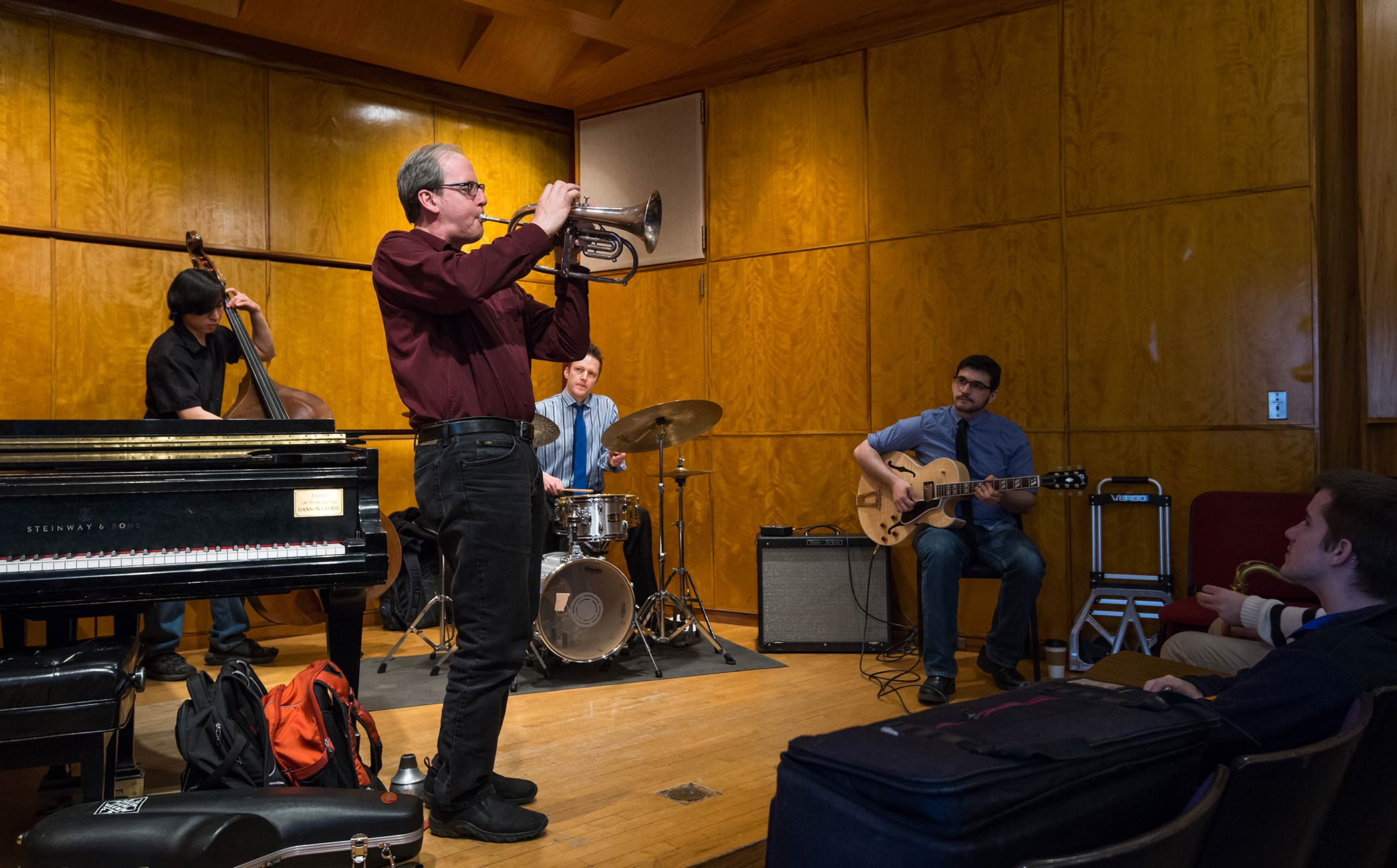 Jeff Beal playing horn in a recital hall with students