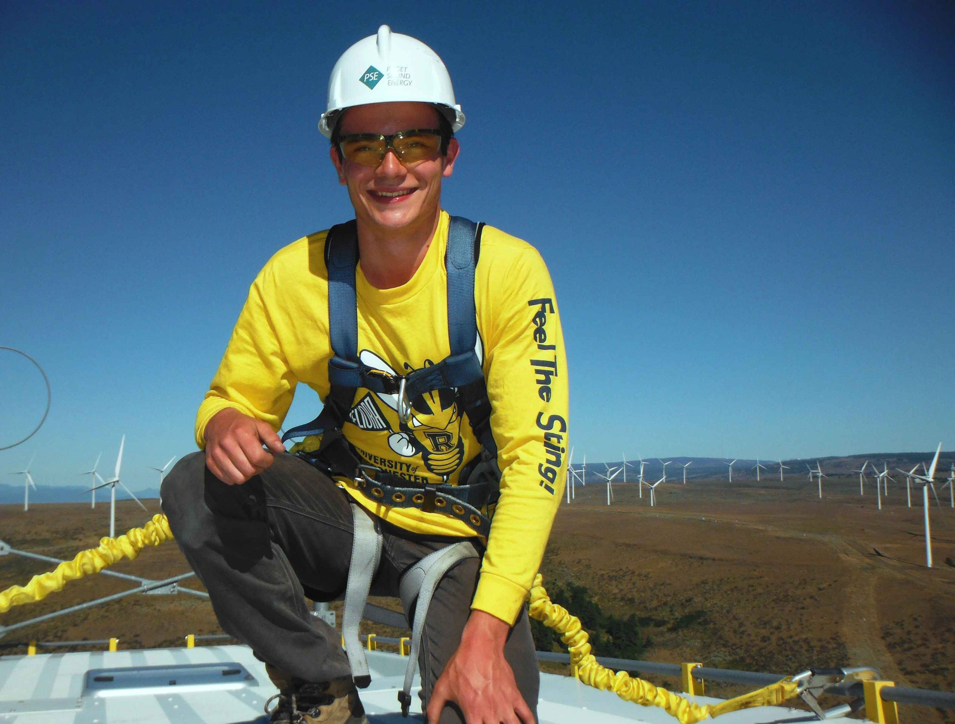 student at a wind farm wearing a Rocky t-shirt