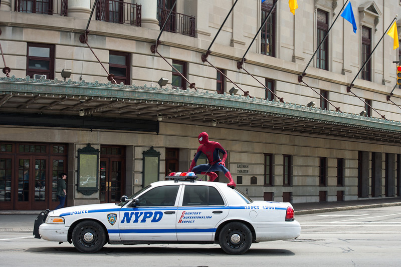spiderman on top of police car in front of Eastman Theatre