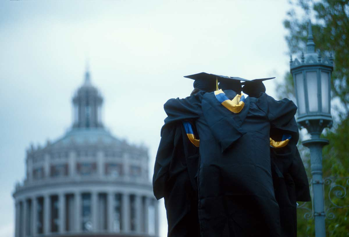 three graduates hugging