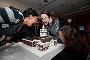 students pretend to eat Rush Rhees Library cake