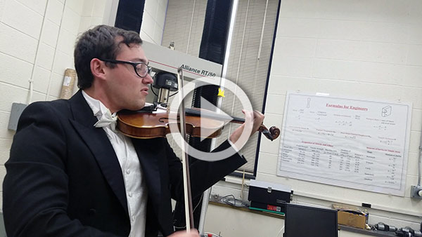 young man in a tux, playing a violin in a lab
