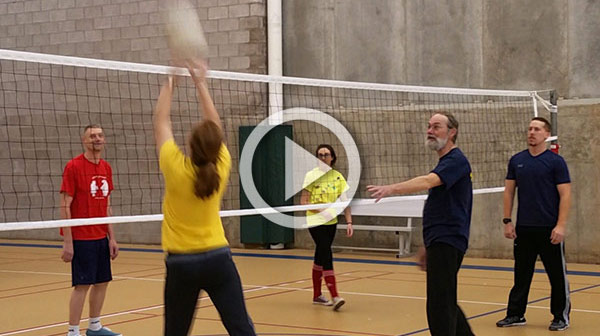 students and professors playing volleyball