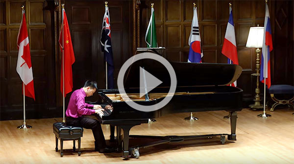 pianist on stage with many countries' flags