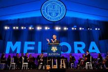 President Joel Seligman applauding at podium
