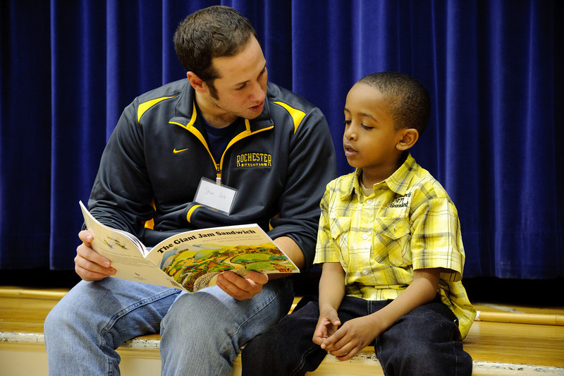 college student reading to little boy