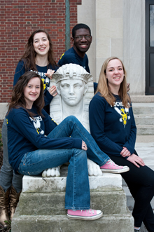 four students sitting near a statue