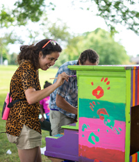 student paints a piano with bright colors