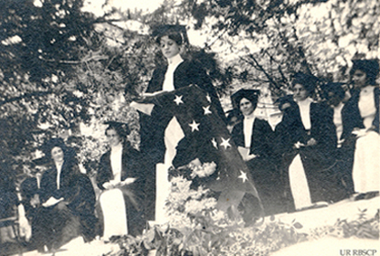 Victorian women grads, one holding an American flag
