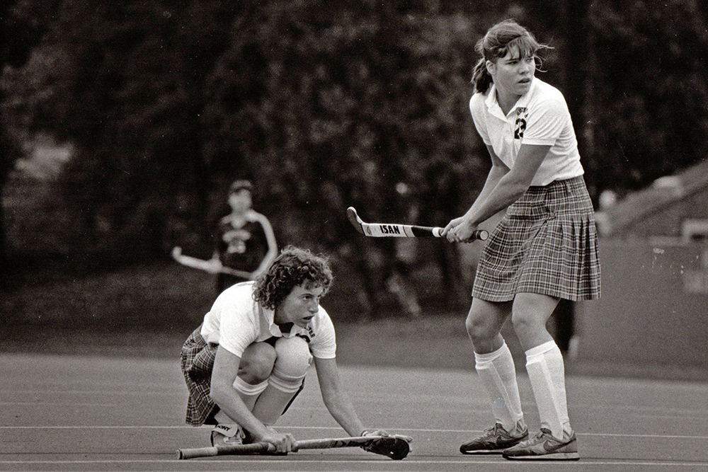 Christine Joor Mitchell and Nancy Melvin Taylor playing field hockey