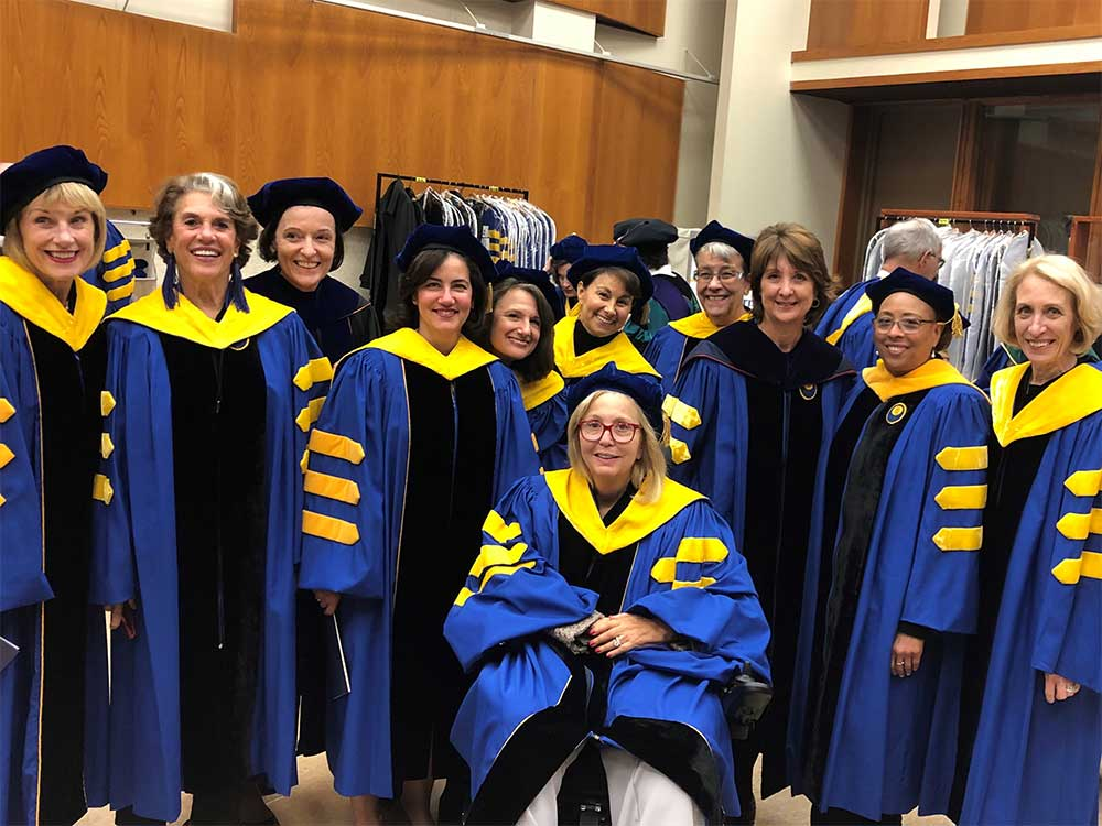 several members of the board of trustees dressed in cap and gown