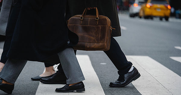 Two men and one woman crossing a New York City crosswalk. Their tailcoats are showing along with their shoes and pants. A brown leather briefcase can be shown held by one of the men. A yellow taxi can be seen in the background, along with a white car ahead of it.
