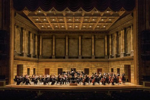 Philharmonic orchestra playing on stage at the Eastman Theatre