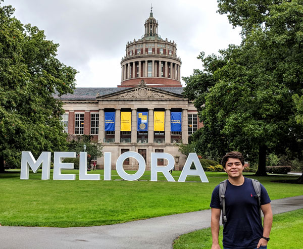 Obed Badillo Moreno '19 standing in front of rush rhees with the large meliora letters in the quad