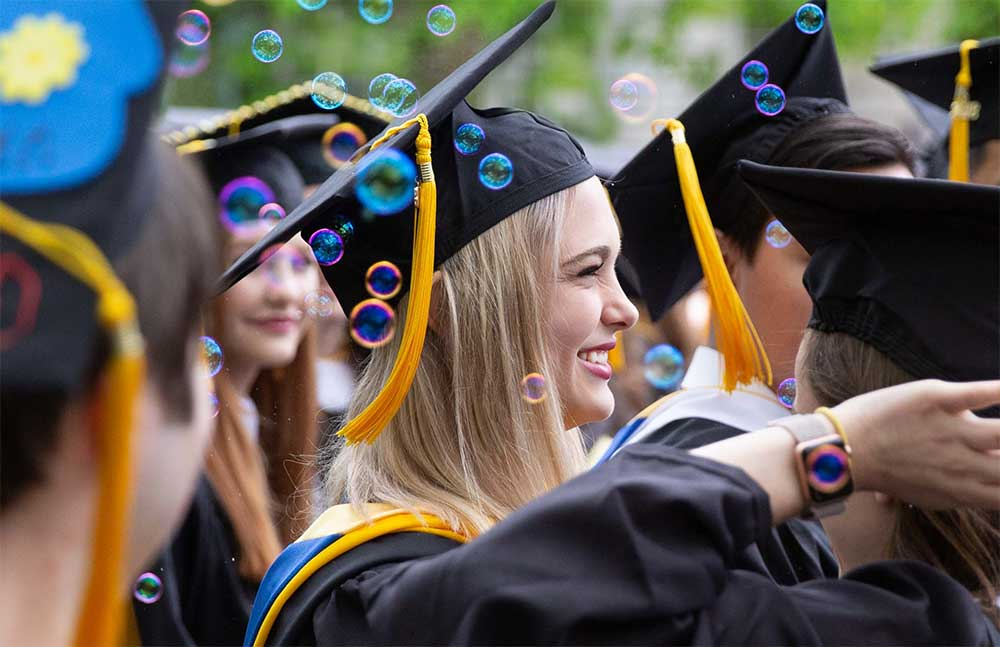students celebrating during graduation wearing cap and gown blowing bubbles