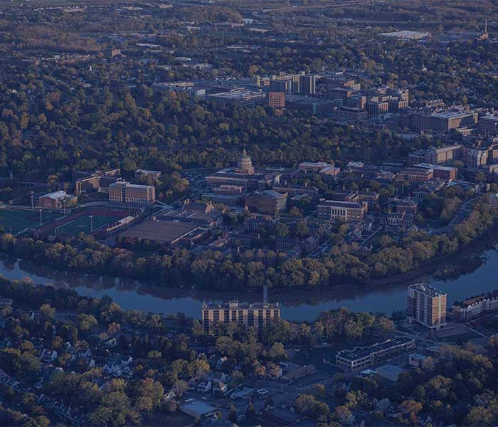 aerial image of both the river campus and medical center campus as well as the genesee river - all with a darkish blue overlay