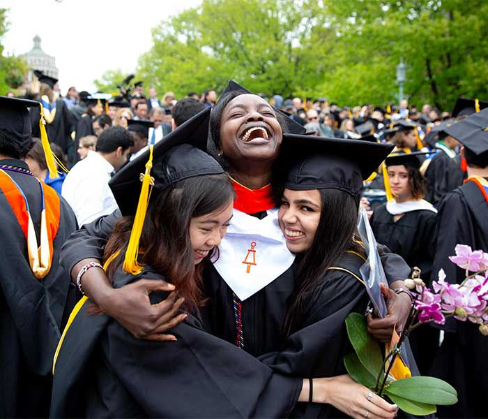 three women in cap and gown celebrating at commencement