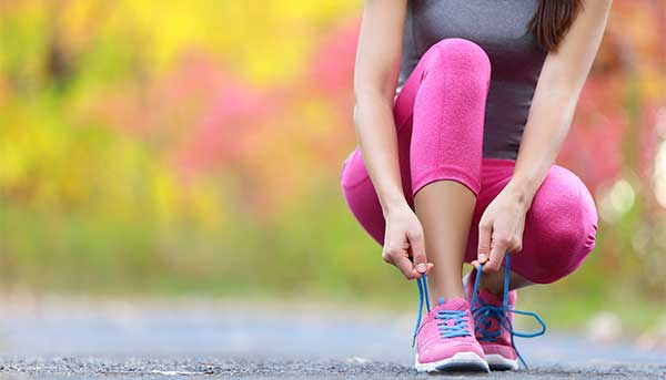 woman in running clothes squatting to tie her shoe