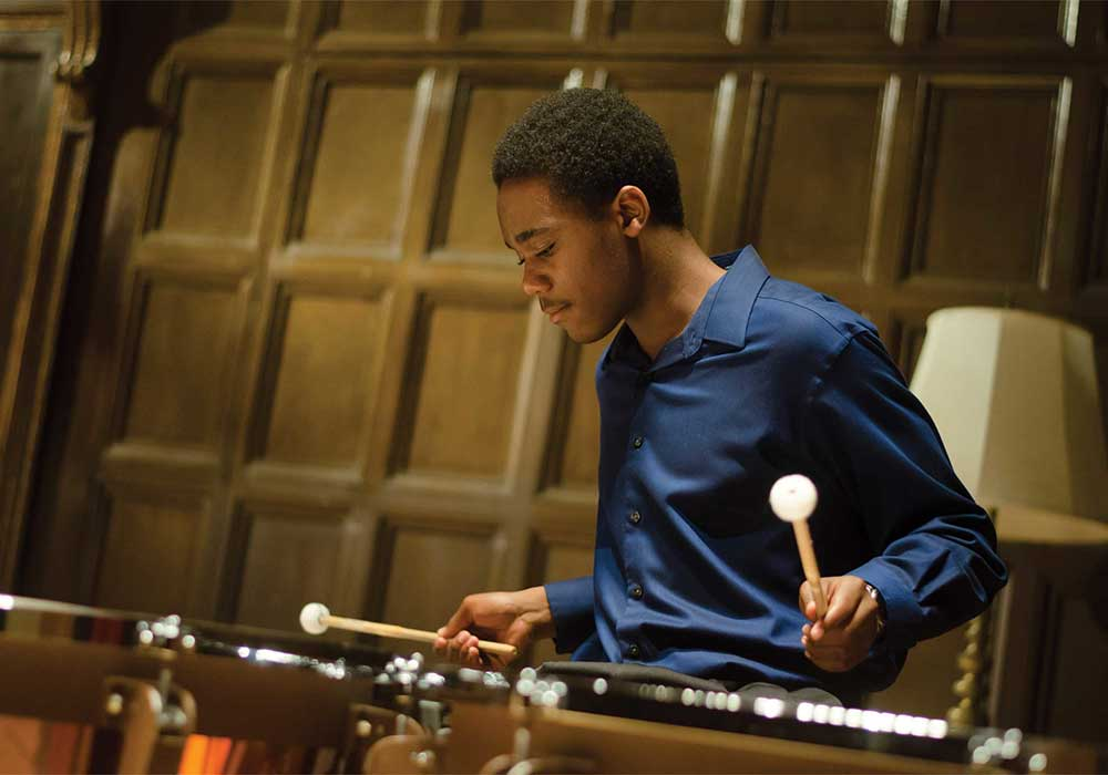 male eastman student in blue shirt playing percussion