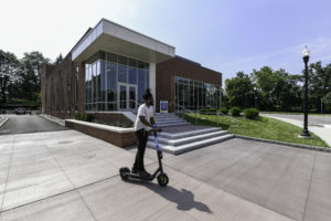 Person on scooter in front of Sloan Center