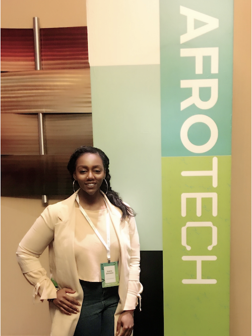 Juana Johnson in front of the AfroTech banner