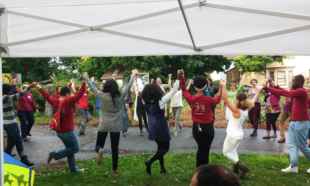 people dancing with arms upraised under a tent