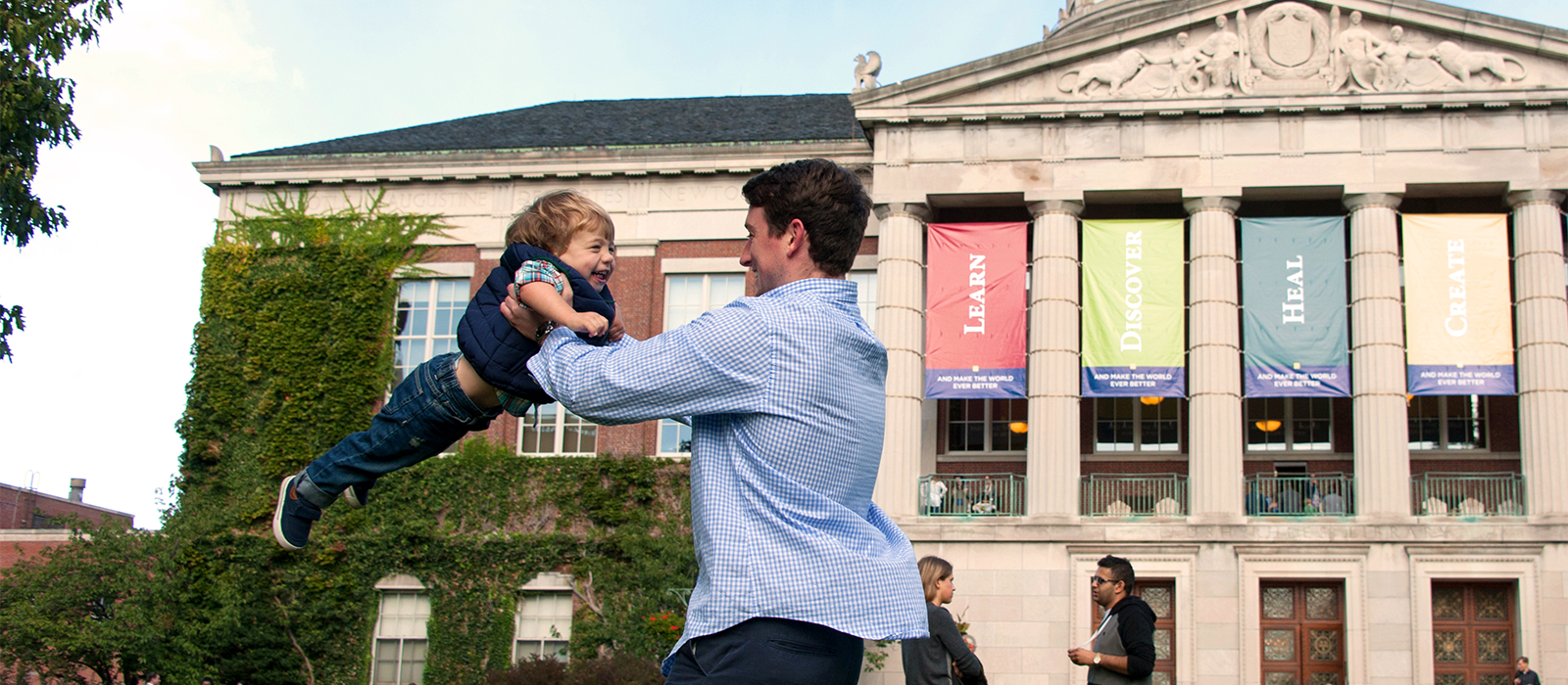 man swinging young son in front of Rush Rhees library