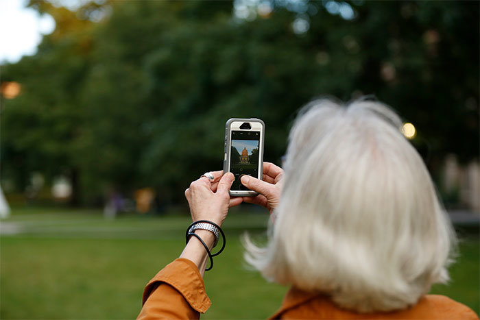 woman taking picture of library with iphone