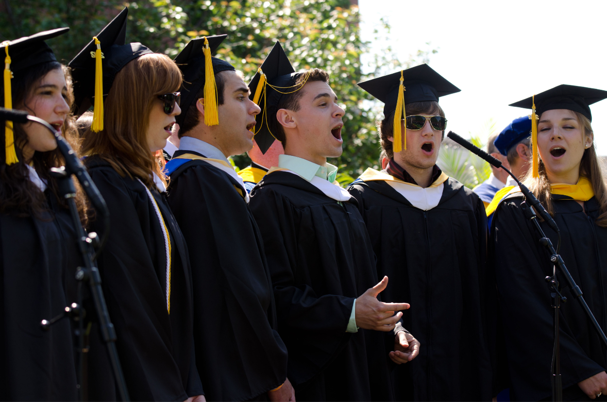 University of Rochester graduates in hat and gown singing the alma-mater at commencement