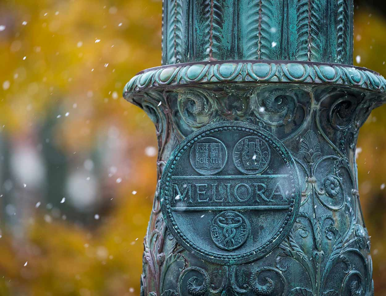 Meliora seal on flagpole in snow at University of Rochester