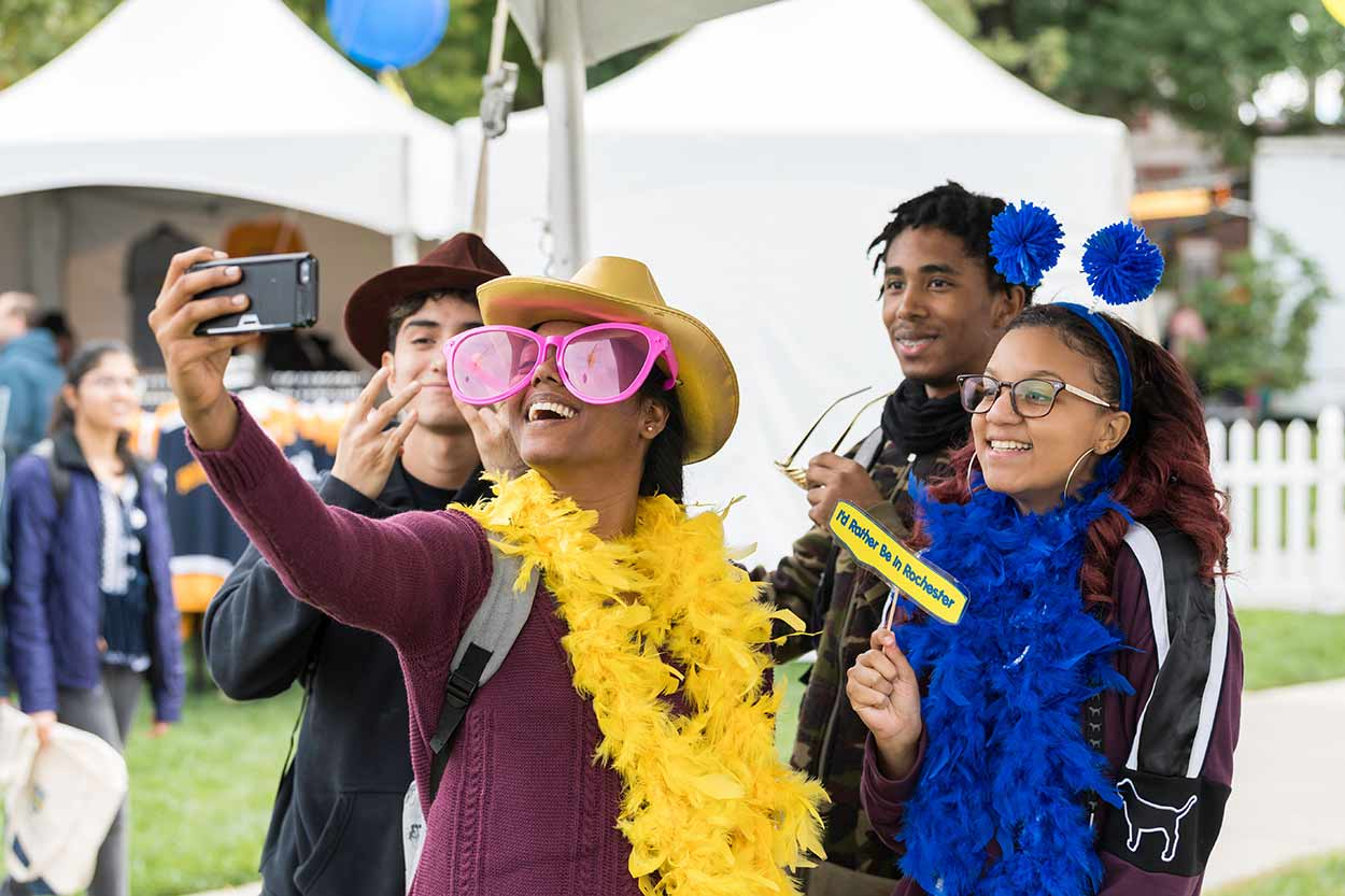 Students wearing costume props taking a selfie at University of Rochester Meliora Weekend