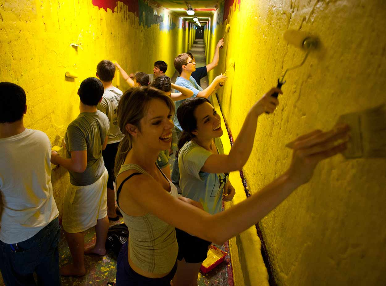 Students painting over graffiti walls in tunnels at University of Rochester