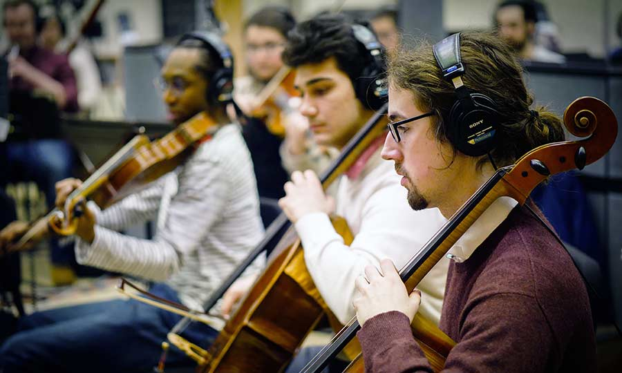 musicians wear headphones while playing cellos and violins