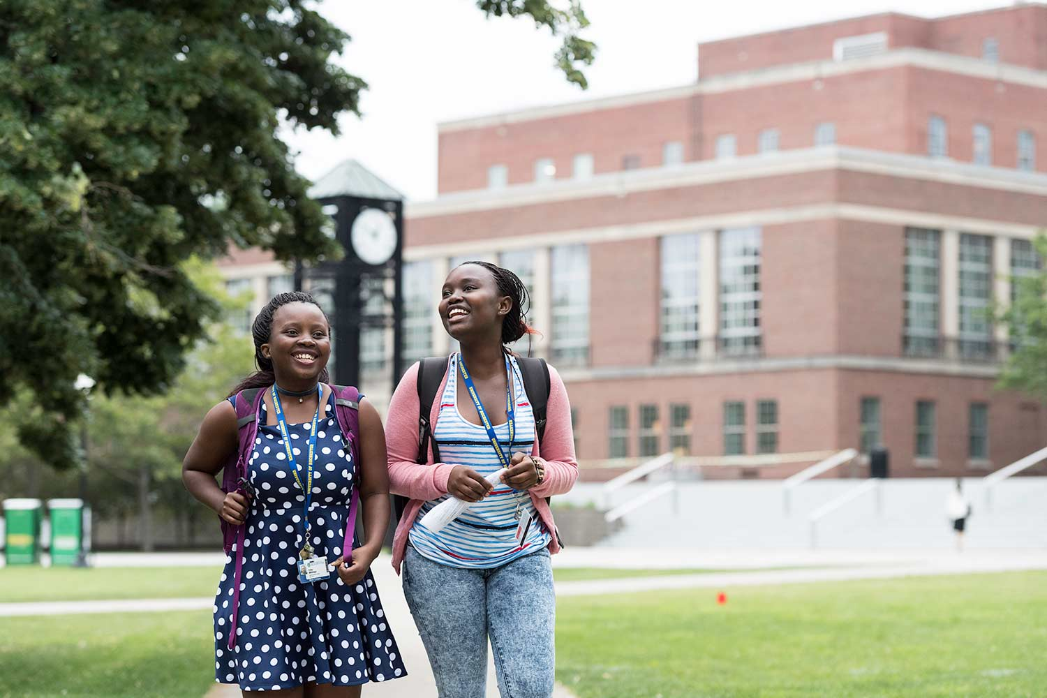 Two students smiling and walking outside at University of Rochester