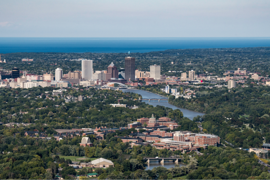 Aerial image of University of Rochester with Rochester skyline in background