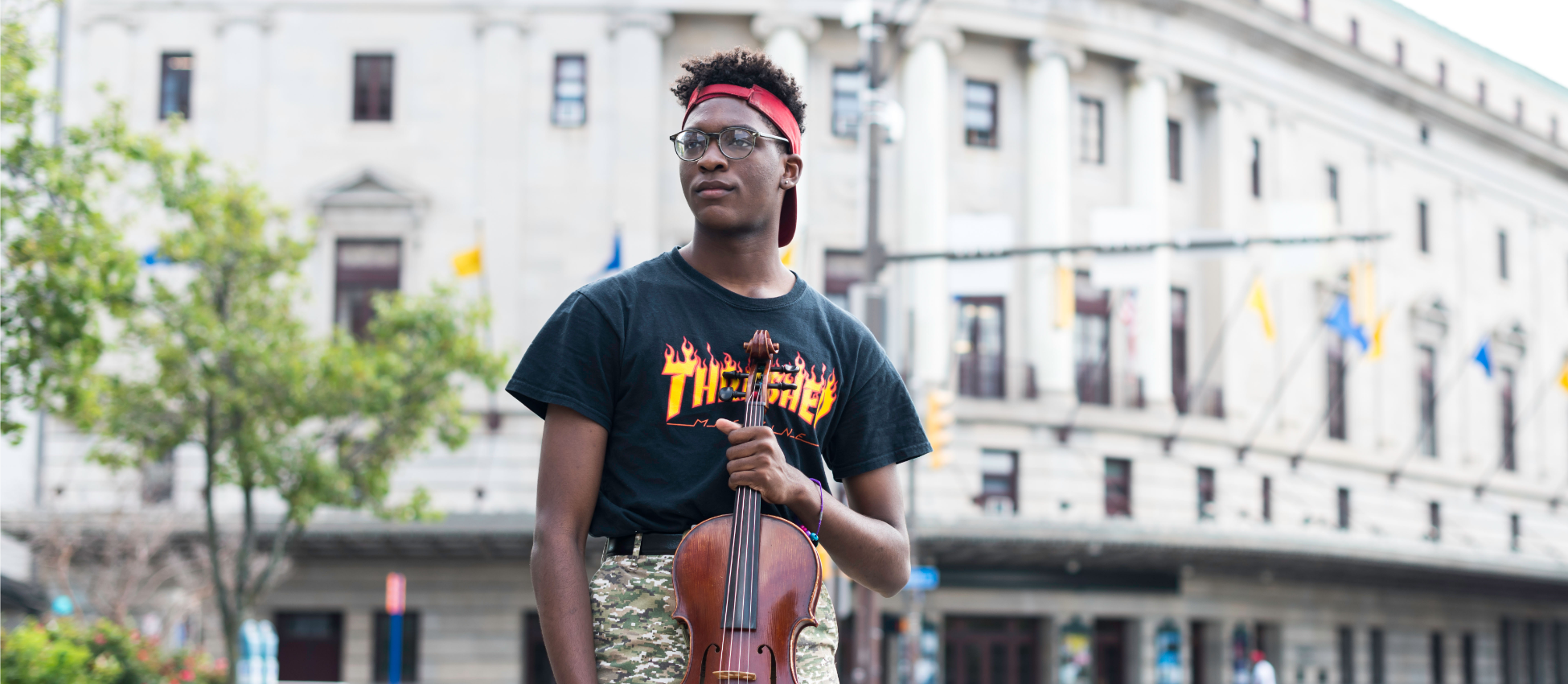 Student holds Violin outside Eastman Theater
