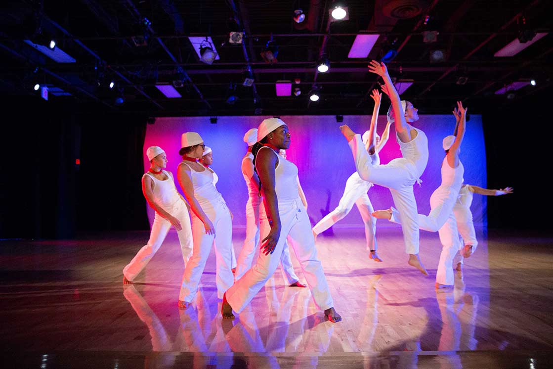 Female dancers in white outfits performing on stage at University of Rochester