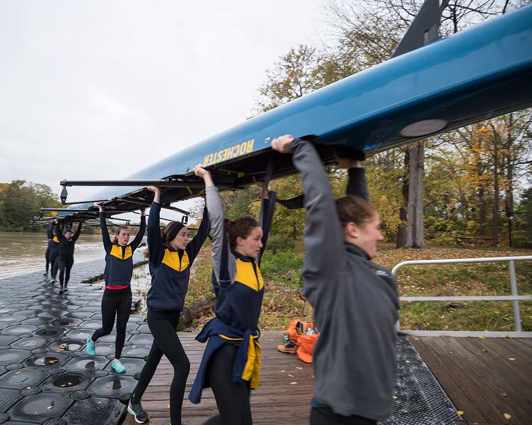 Women's rowing team carrying boat to Genesee River at University of Rochester