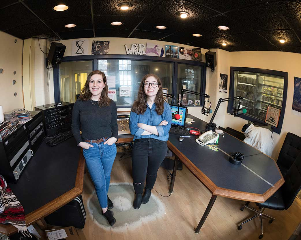 Two students stading inside WRUR campus radio station booth at University of Rochester