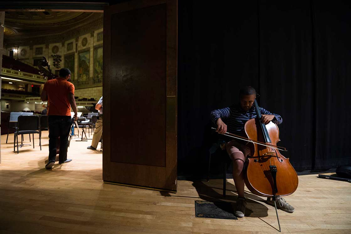 Student with cello warming up back-stage at University of Rochester Eastman School of Music
