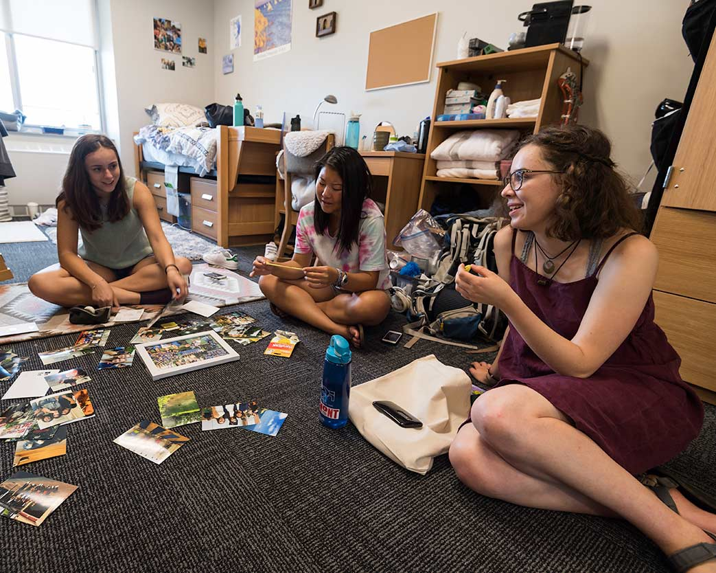 Three students sitting on floor looking at pictures in dorm room at University of Rochester