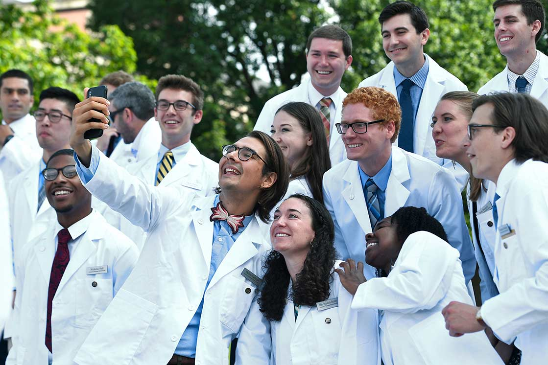 Graduate students taking selfie at University of Rochester School of Medicine and Dentistry white coat ceremony