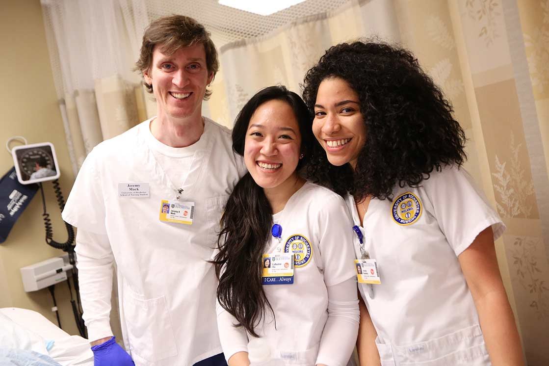 Three students at hospital beside at University of Rochester School of Nursing