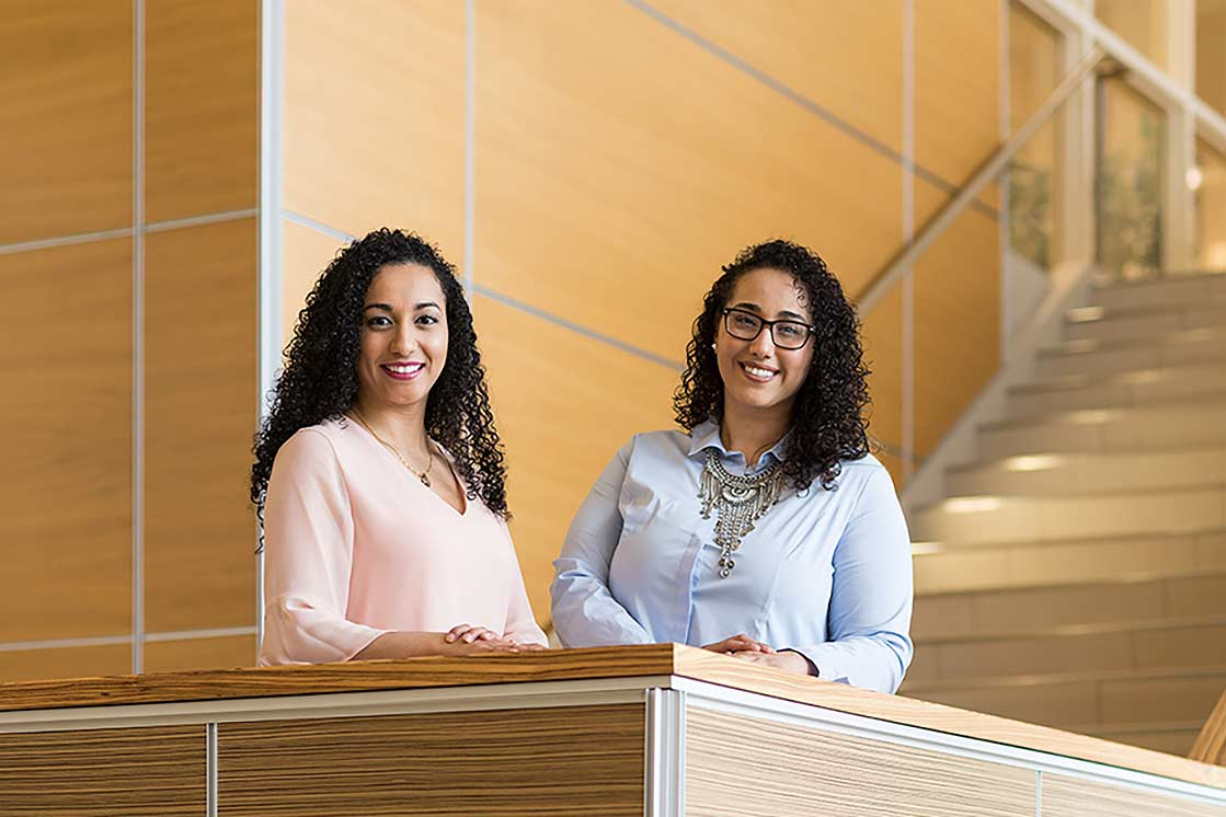 Two women smiling from balcony at University of Rochester Warner School of Education